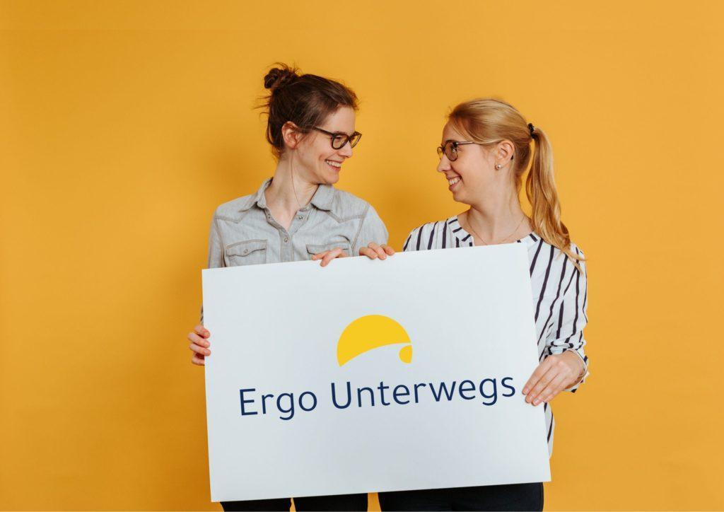 Sarah und Sara lachen sich an und halten ein großes Schild auf dem das Ergo Unterwegs Logo abgebildet ist.