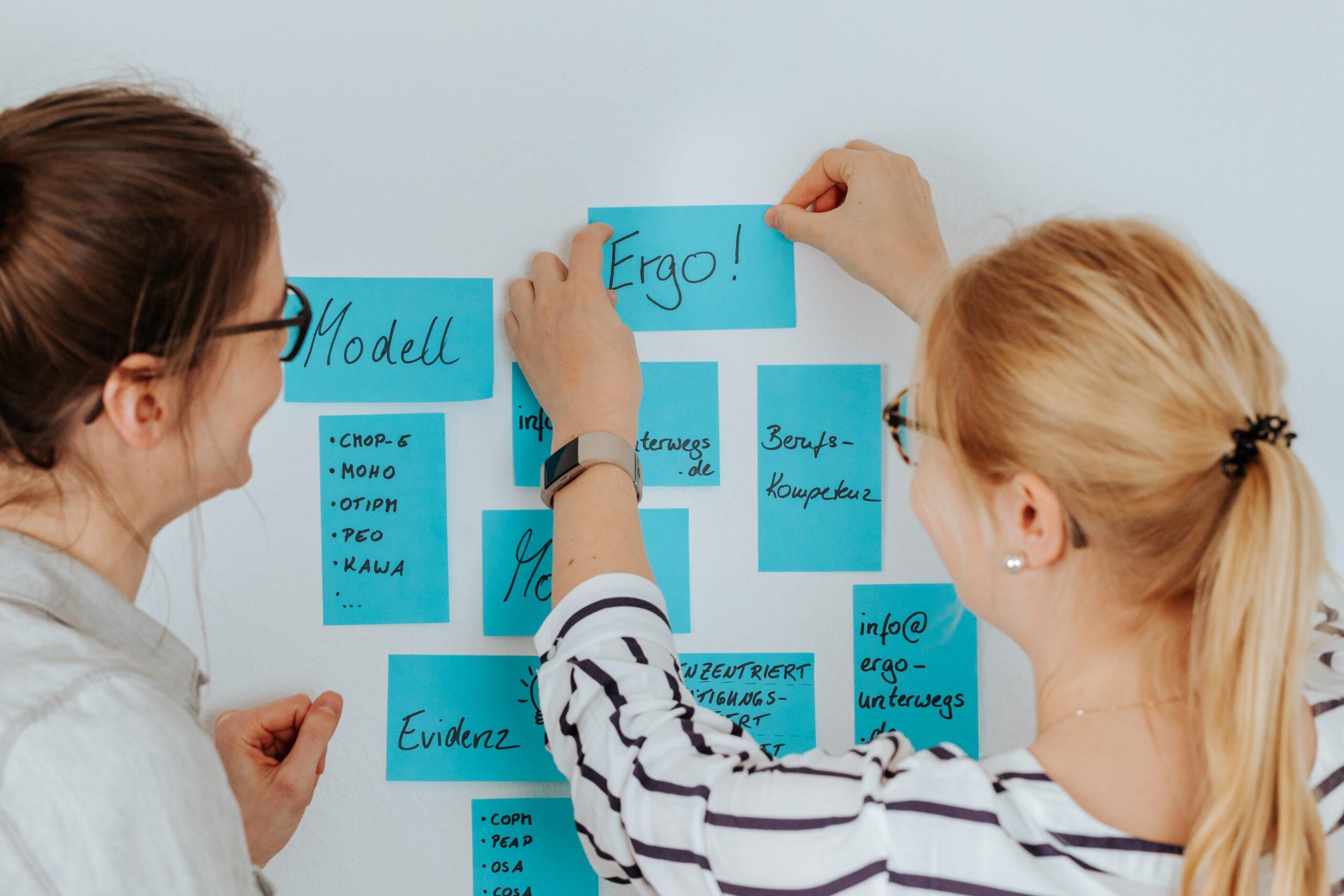 Sarah und Sara kleben Postits an eine Wand. Auf den Postits steht Ergo, Modell, Betätigungsorientierung, Ergotherapie usw.