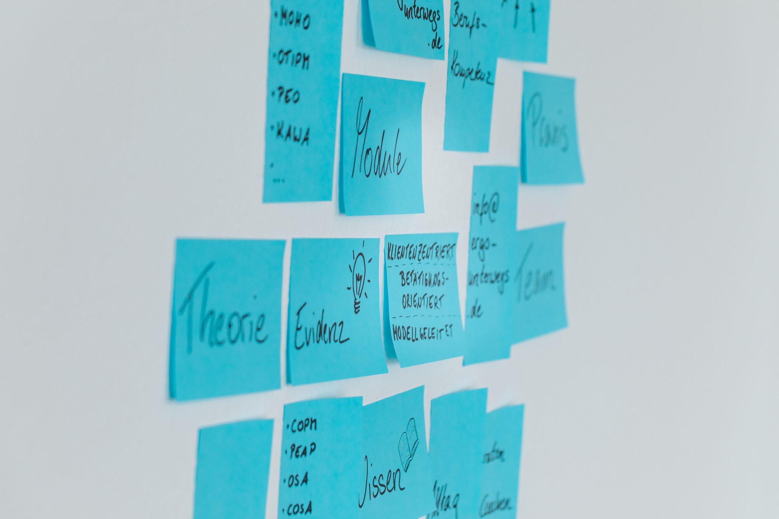 Blaue Postits kleben an einer weißen Wand. Auf den Postits ist das Ergo Unterwegs Logo zu sehen, außerdem die Begriffe Evidenz, Ergotherapie usw.