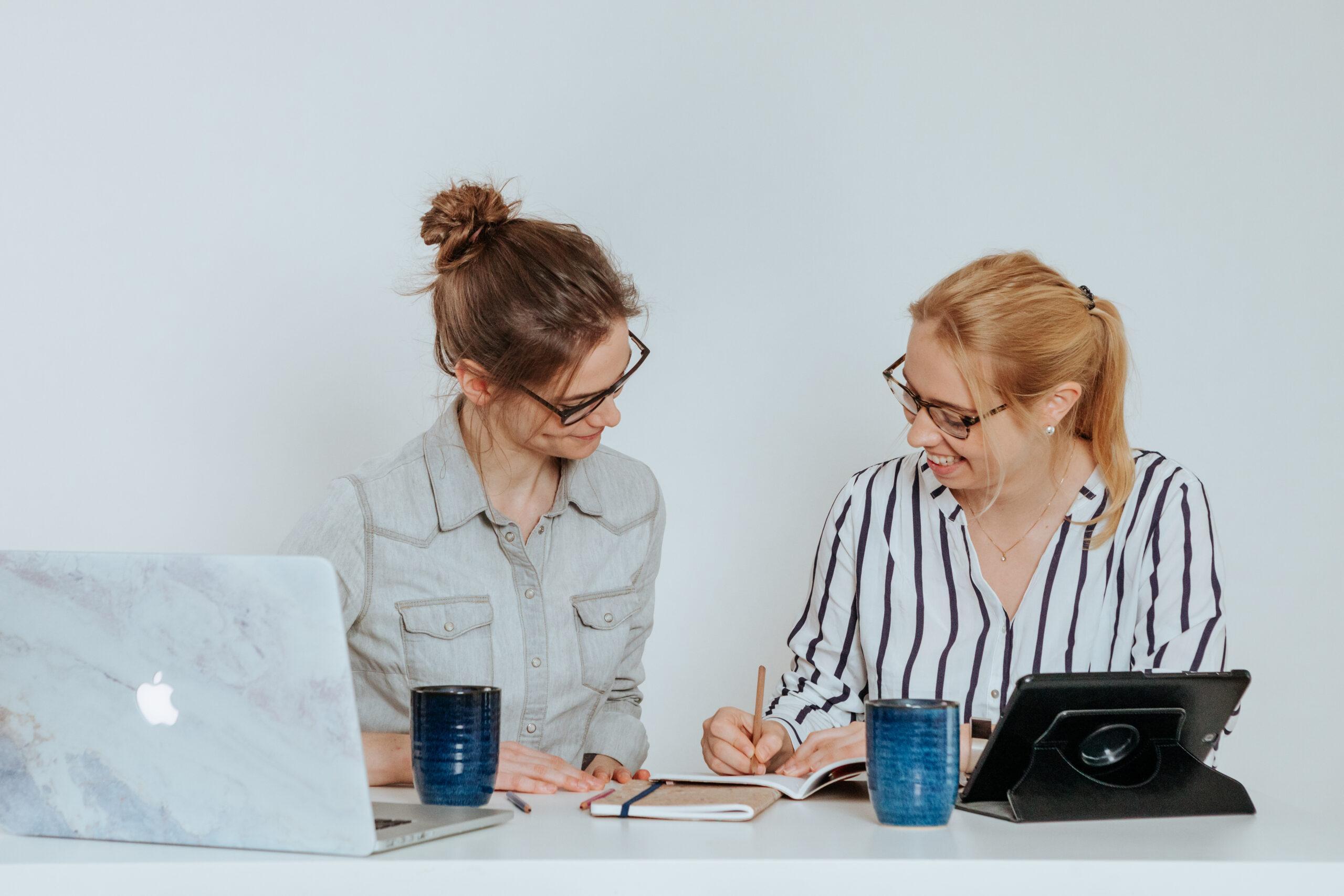 Sara und Sarah sitzen an einem Schreibtisch und schauen gemeinsam auf Unterlagen.