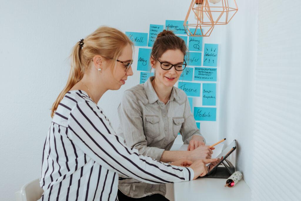 Sara und Sarah sitzen an einem Schreibtisch und schauen gemeinsam auf ein Tablet. Im Hintergrund hängen Postits an der Wand mit der Aufschrift: Ergotherapie, Evidenzbasierung, Klientenzentrierung, Betätigungsorientierung usw.