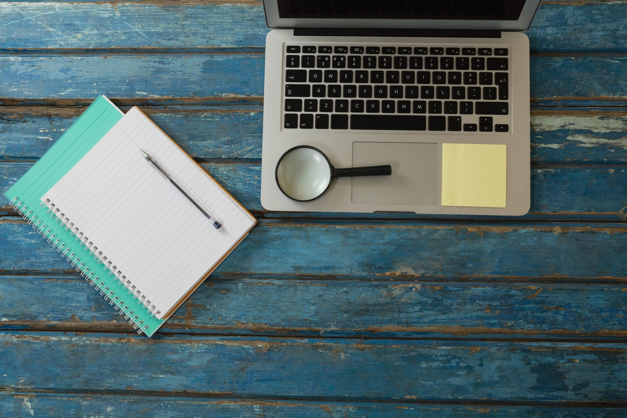 Ein blauer Holztisch, auf dem ein Laptop, eine Lupe und Notizbücher liegen.