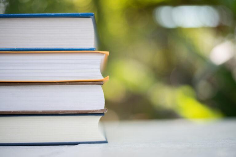 Ein Bücherstapel vor einem unscharfen Hintergrund.