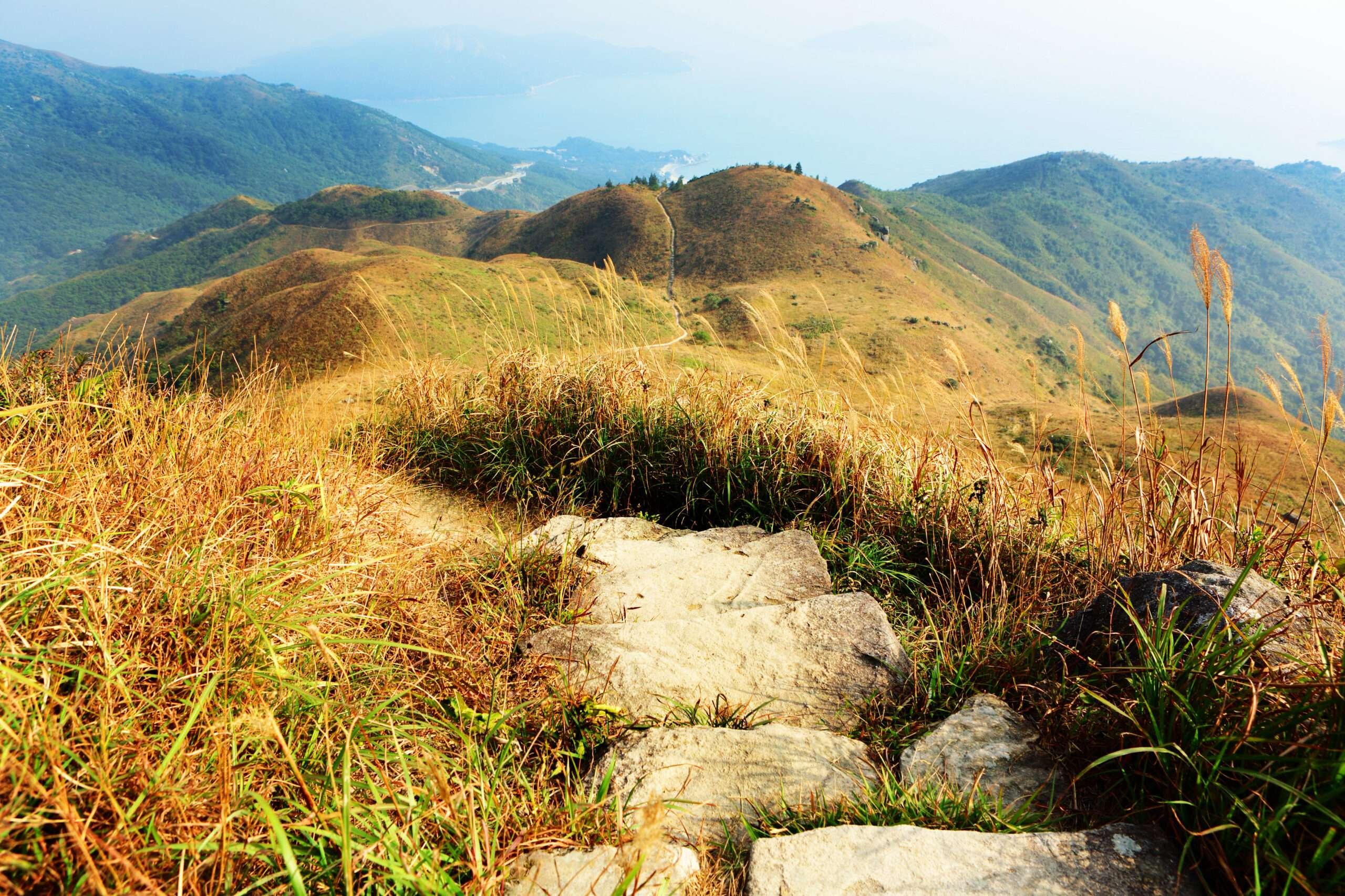 Ein Wanderweg, der über Bergrücken in die Ferne verläuft.