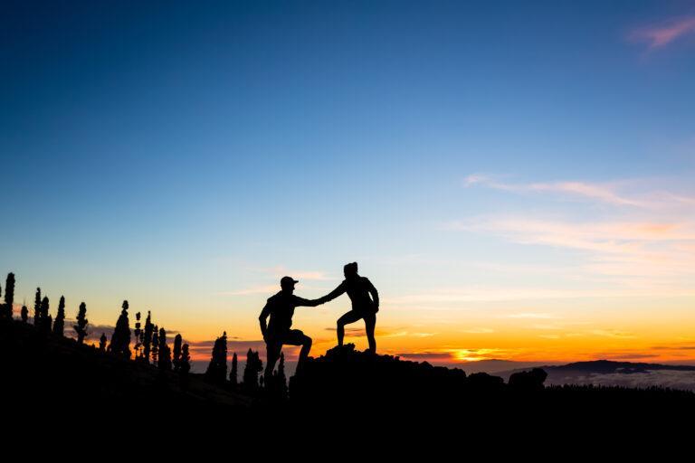 Die Schattenrisse von zwei Bergsteigenden, die sich die Hand geben vor einem Sonnenuntergang.